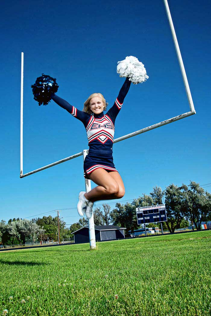 senior picture of cheerleader jumping in front of football goal posts