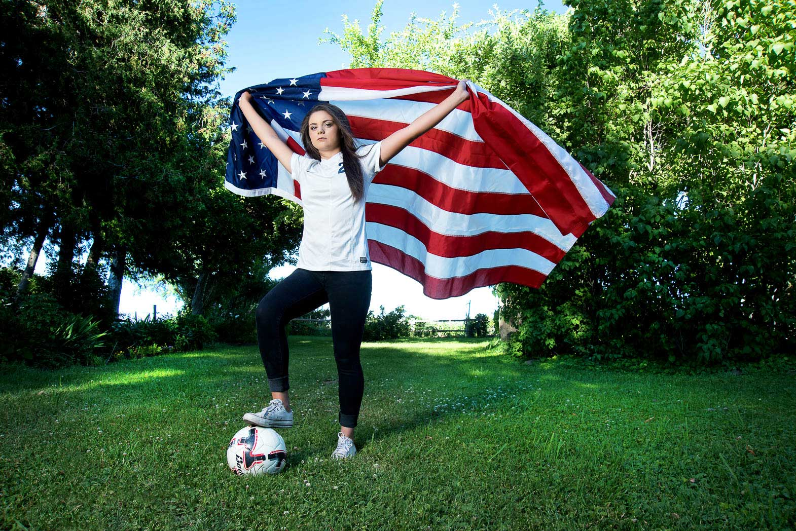 senior picture of girl standing with foot on soccer ball and holding american flag billowing behind her