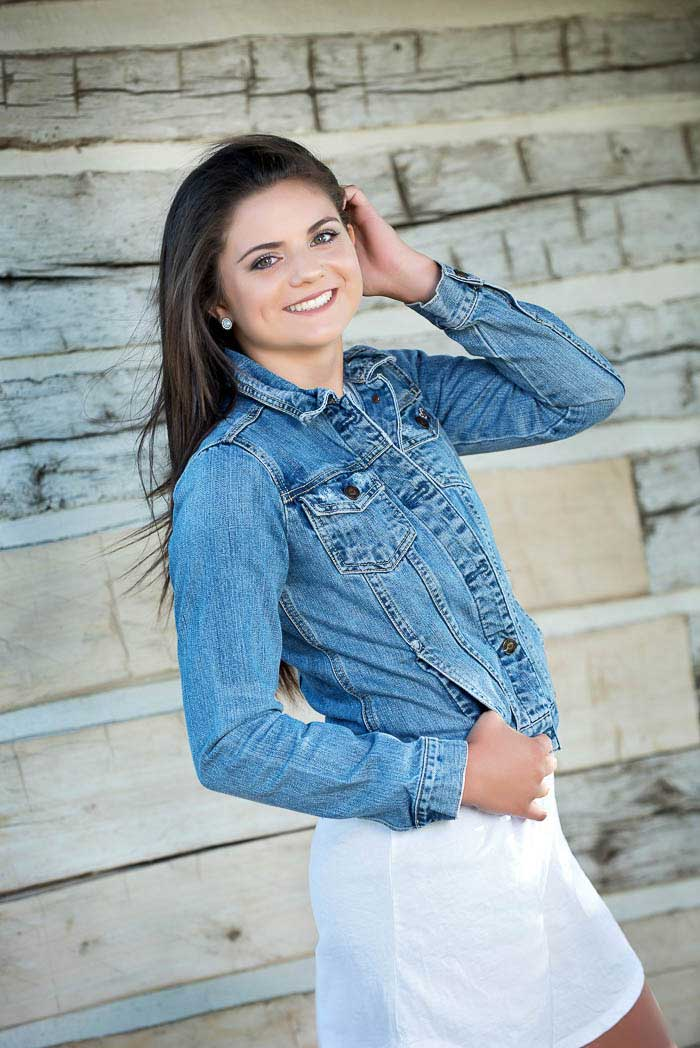 Senior picture of girl wearing denim jacket standing in front of rustic cabin wall