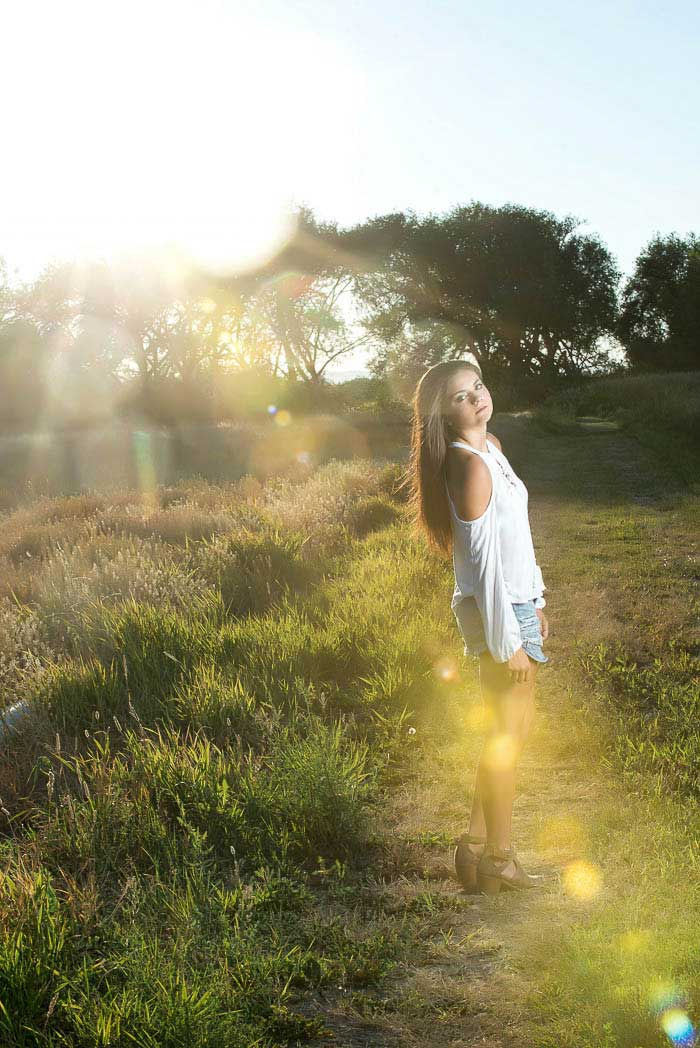 High school senior girl standing in a meadow with golden light around her