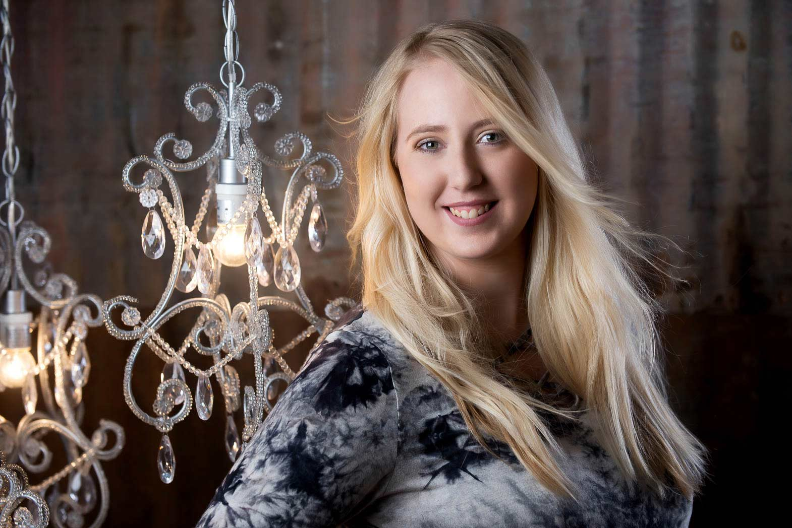 studio senior portrait of smiling girl standing in front of chandeliers