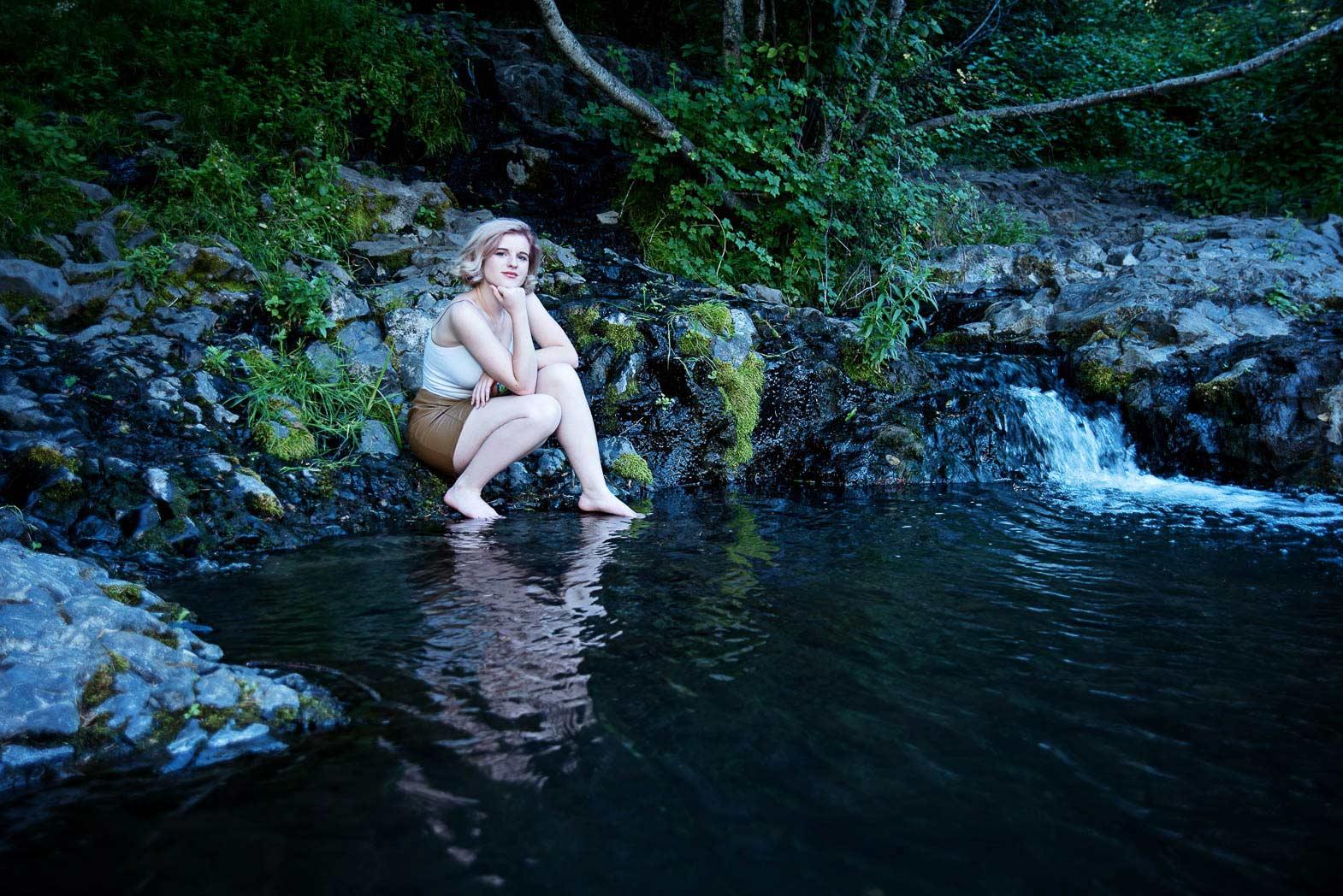 wilderness senior picture of girl sitting beside beautiful lake