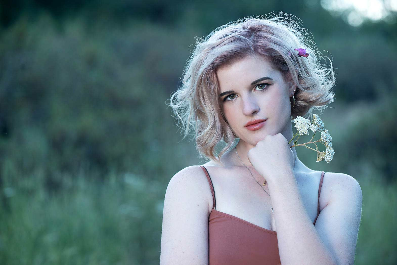 wilderness senior picture of girl with wildflowers standing in front of green background