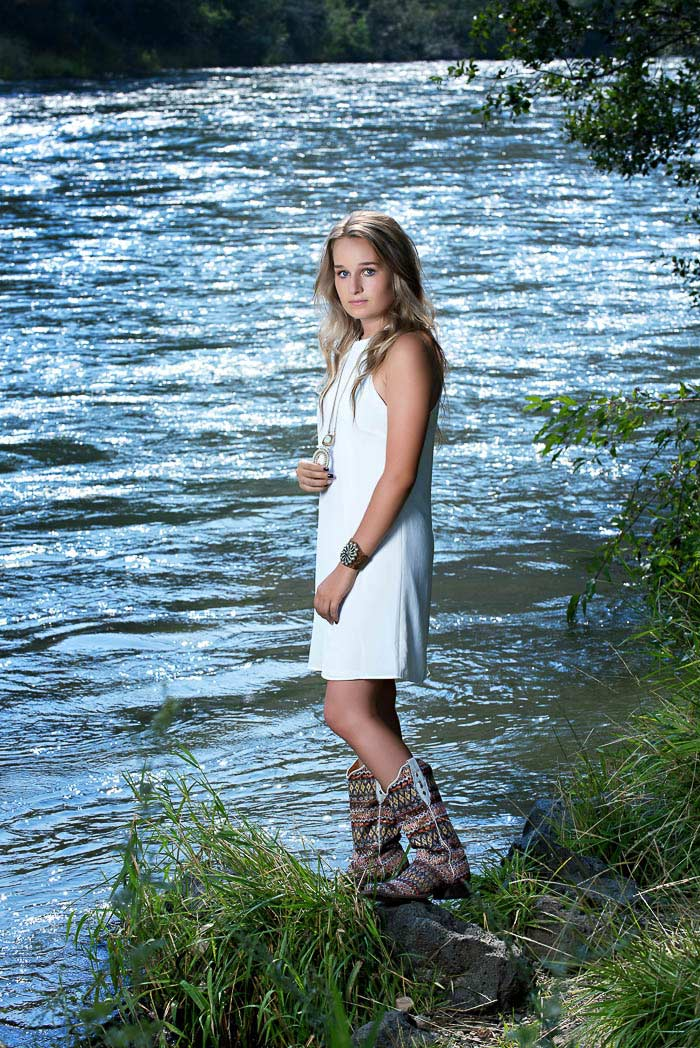 cowgirl senior pictures of girl standing by river wearing white dress and fancy cowboy boots