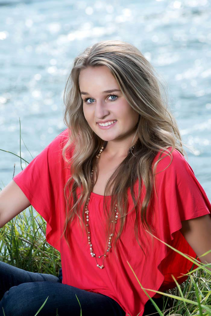 smiling senior girl sitting by a river wearing bright red shirt for cowgirl senior pictures
