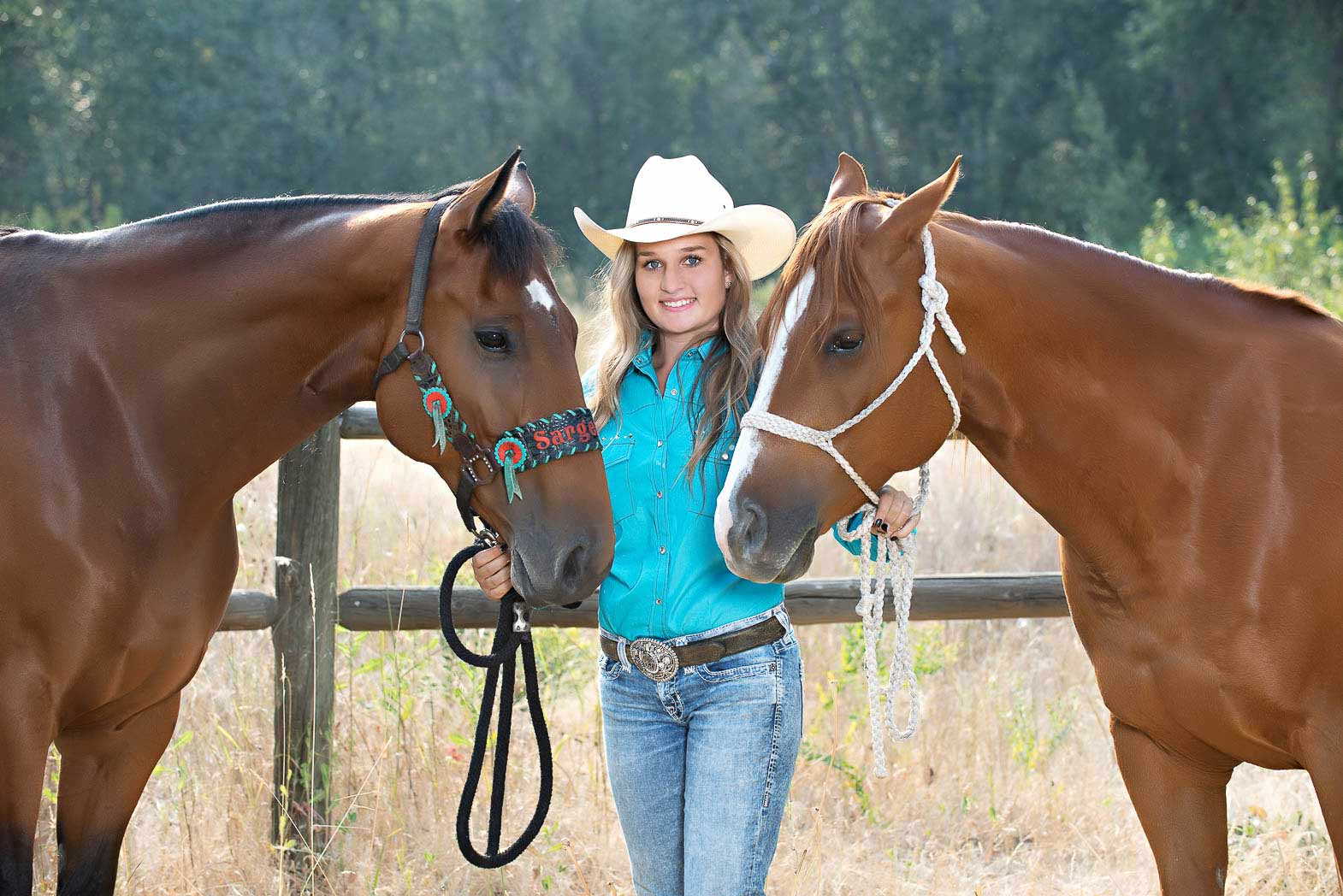 cowgirl senior picture of western girl standing between two horses