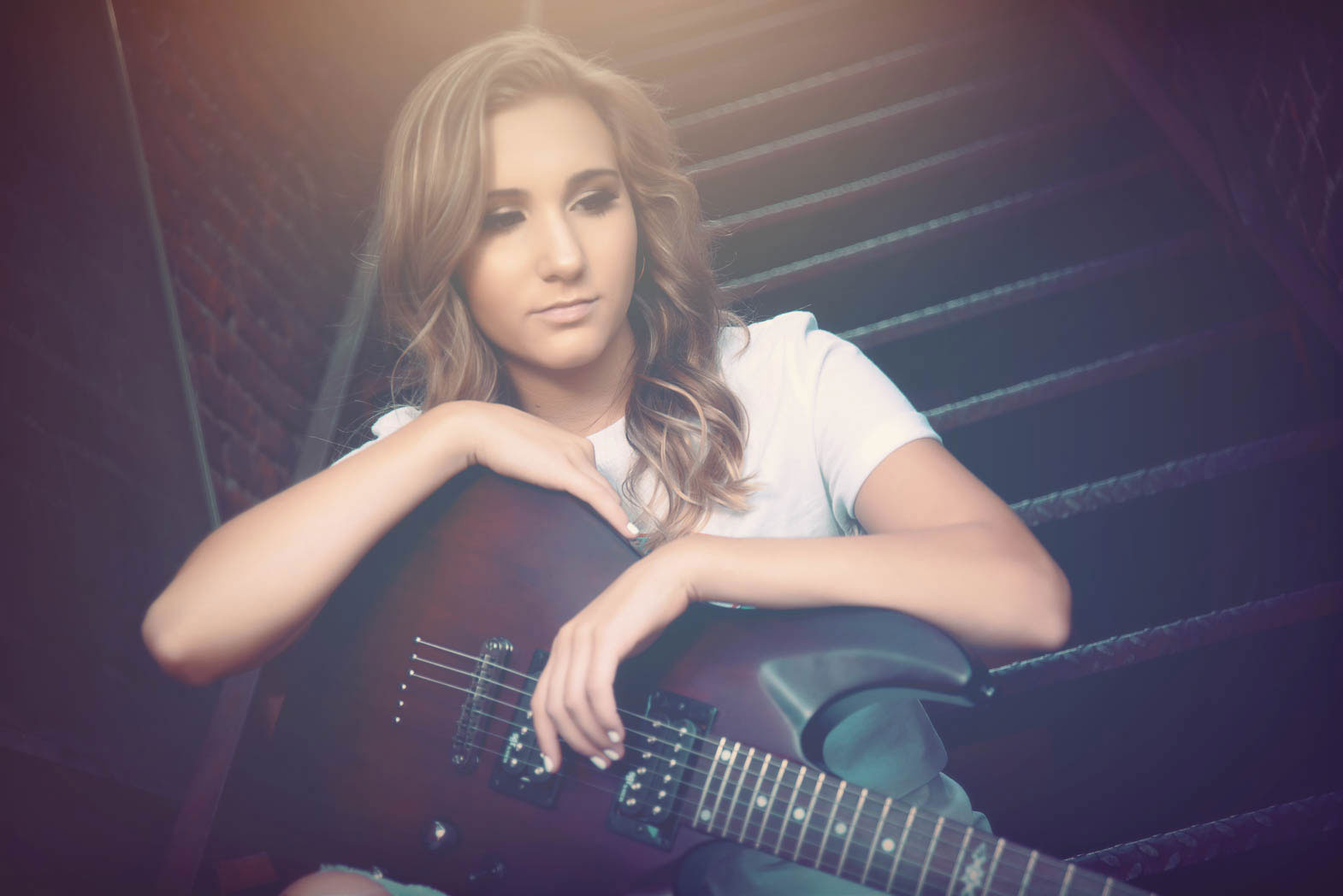 senior portrait of girl looking down sitting on stairway holding a guitar