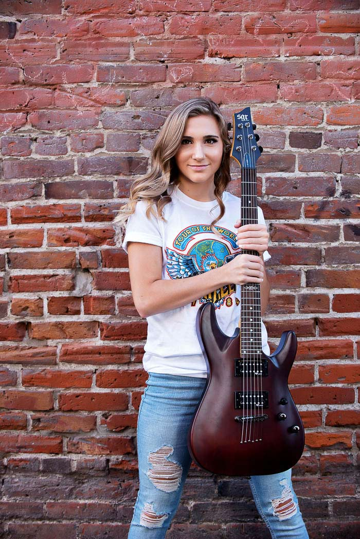 senior picture of girl standing in front of brick wall holding a guitar