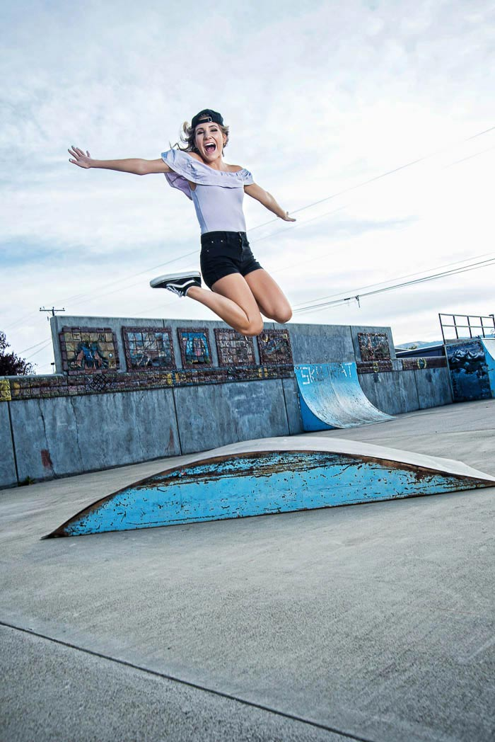 senior picture of girl at skatepark jumping very high with her feet kicked up