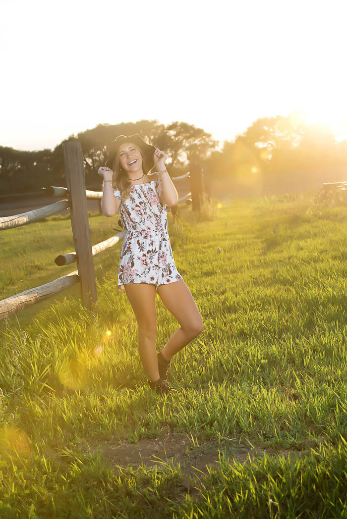 senior portrait of girl laughing by rustic fence at sunset