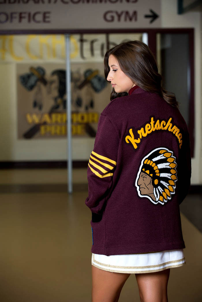 senior portrait of girl in school hallway wearing letterman's sweater