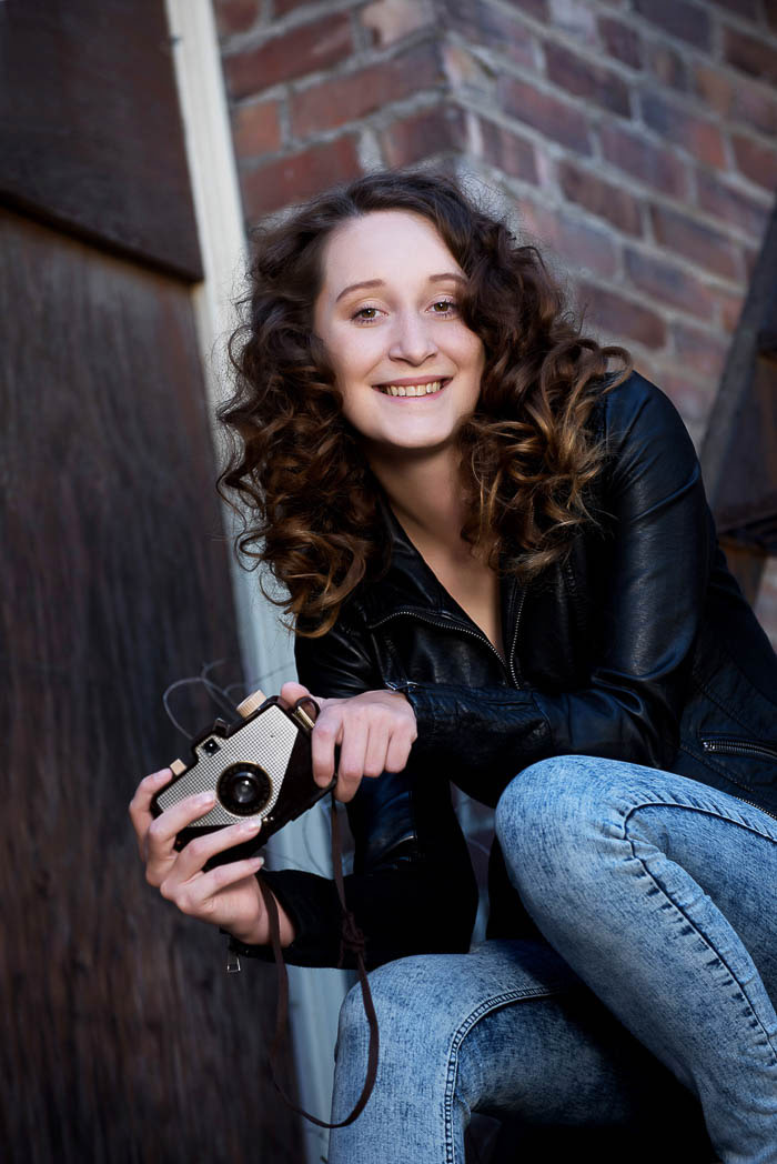 senior picture of girl smiling and holding a camera