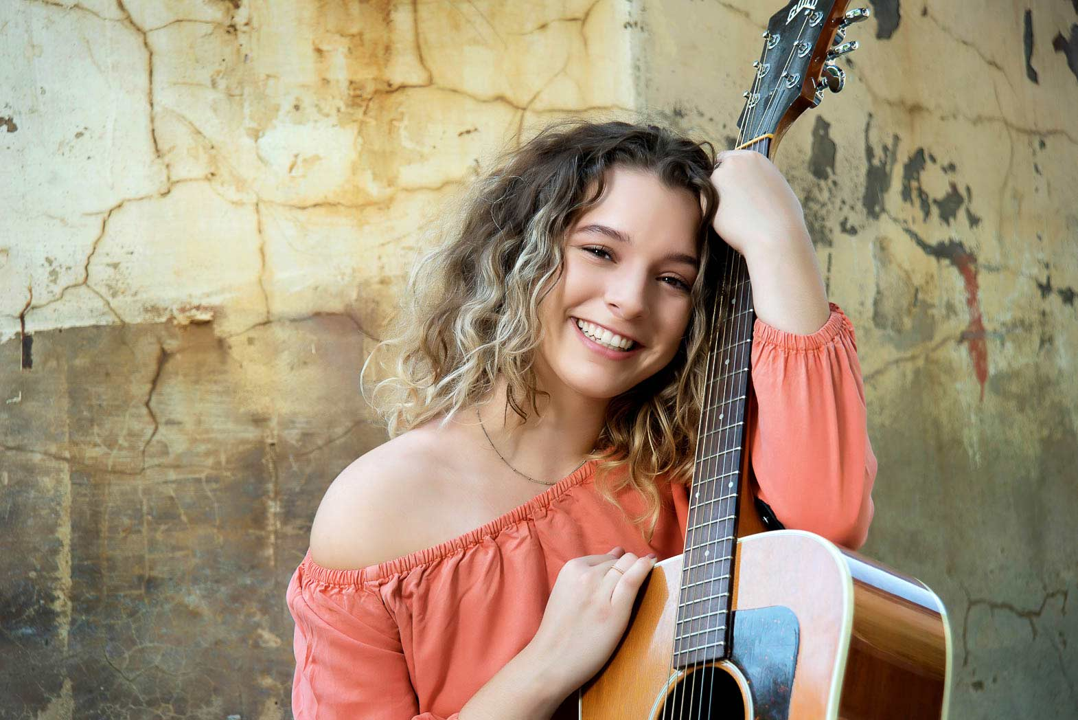 young girl smiling holding onto her guitar in her natural senior portraitss
