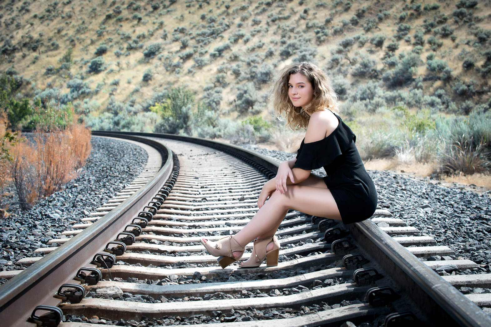 natural senior portraits of girl sitting on the curve of a railroad track
