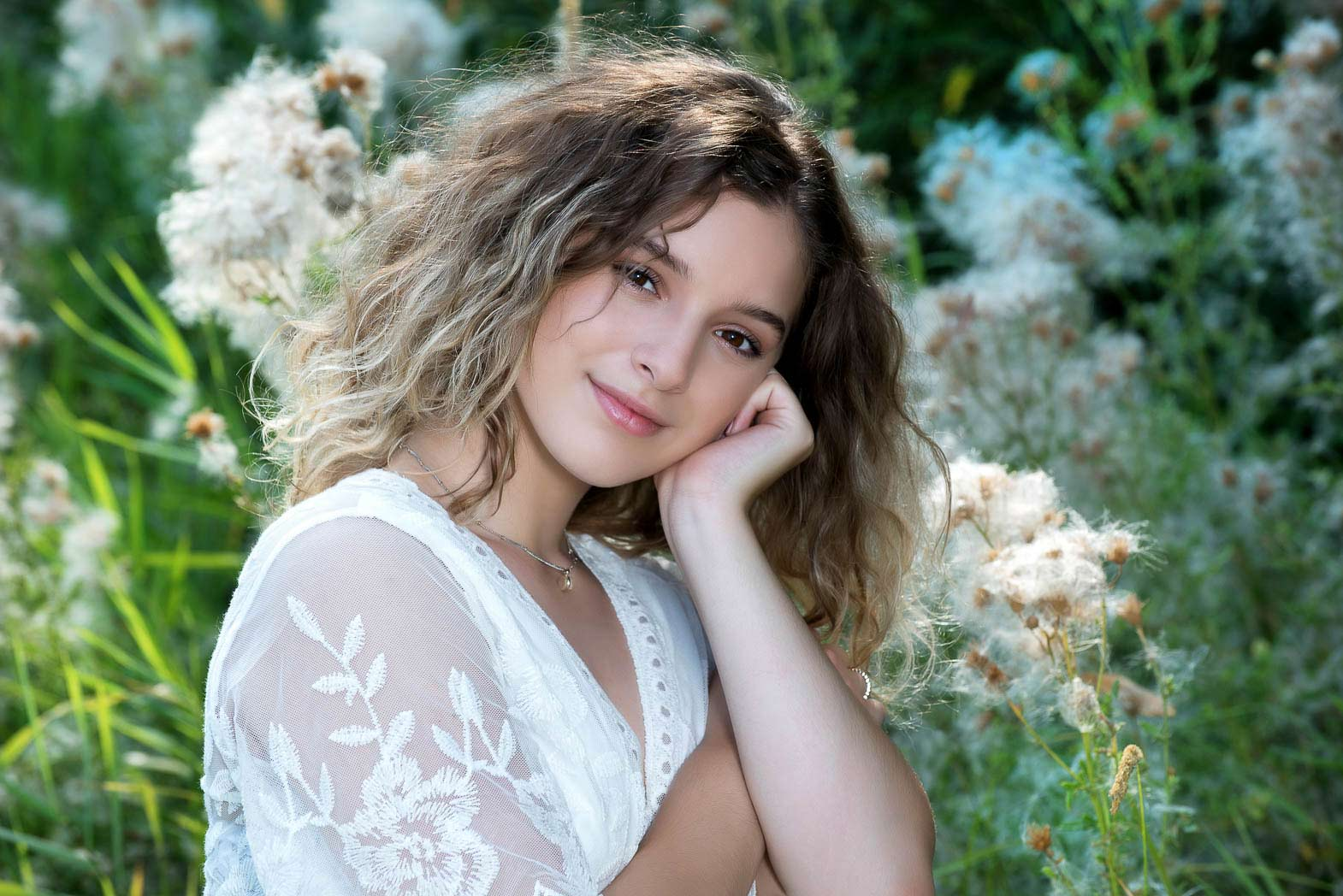 natural senior portraits of girl in white lace with soft smile and summer foliage