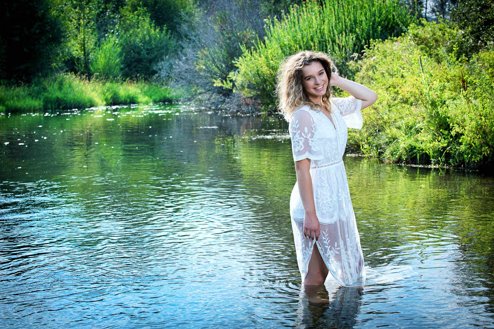 natural senior portraits of girl wearing white lace dress standing in beautiful stream