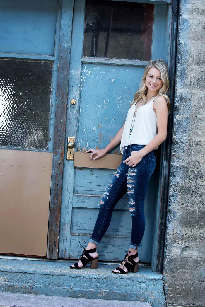 girl standing in urban doorway smiling