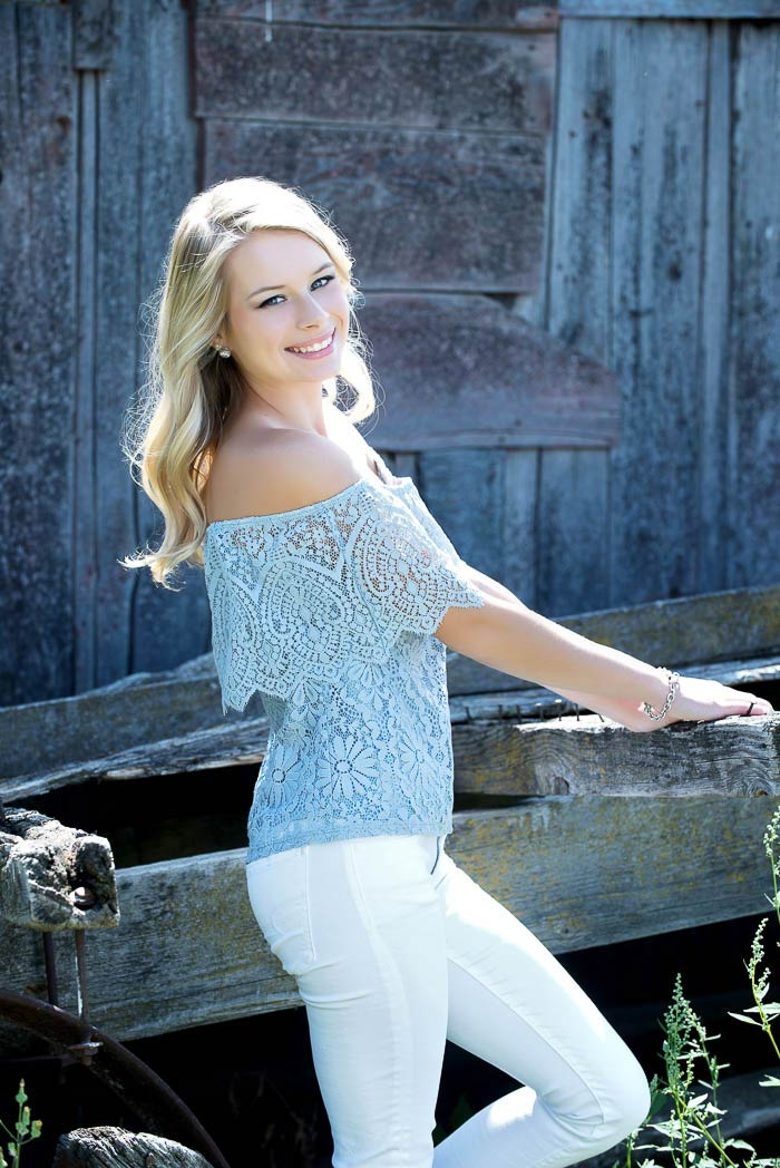 senior model smiling in front of rust barn during senior pictures
