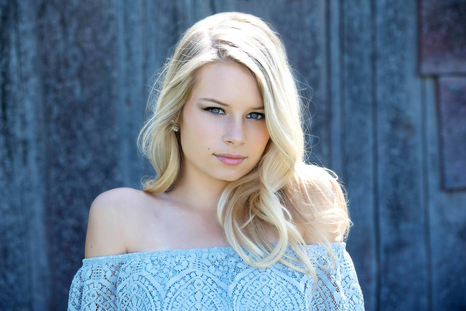 beautiful blond senior model with blue eye and shirt against a blue wall