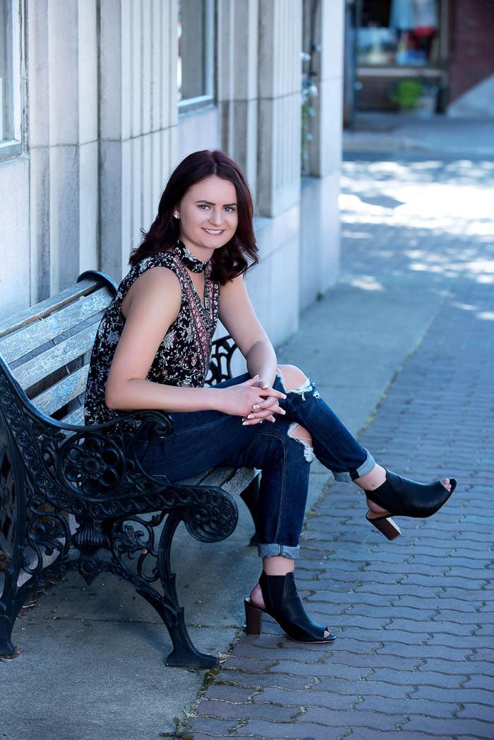senior portrait of girl sitting on park bench on city street in ellensburg