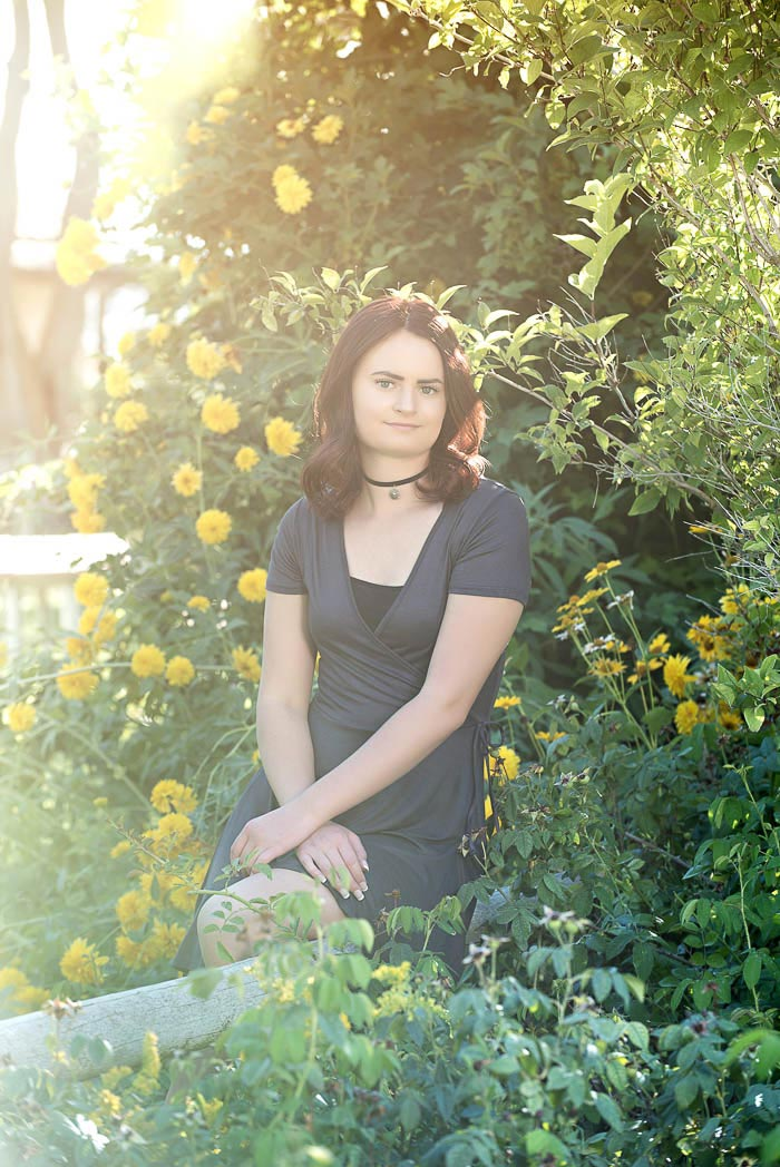 senior picture of girl sitting on fence surrounded by yellow flowers