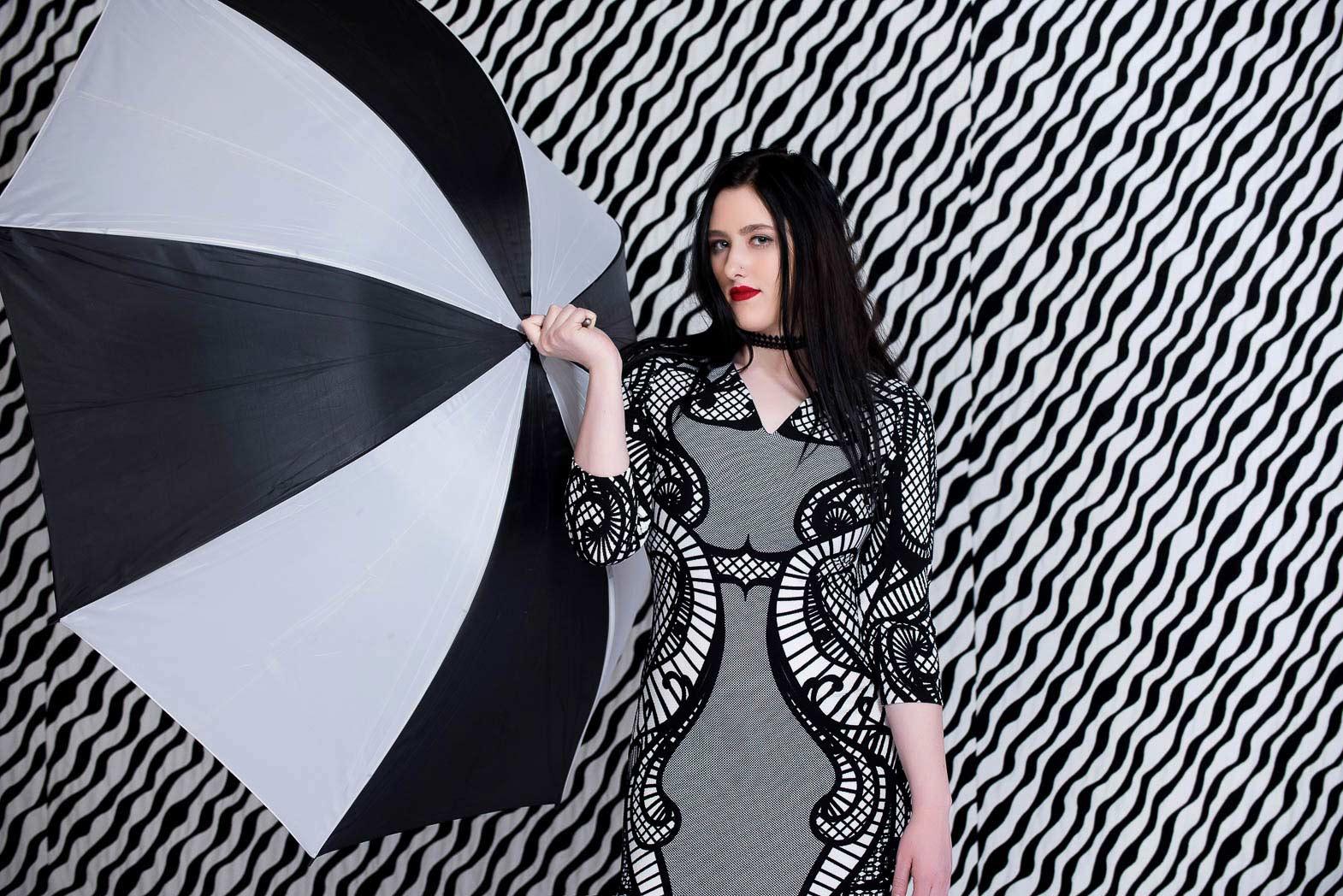 senior girl dressed in black and white holding umbrella during studio model shoot