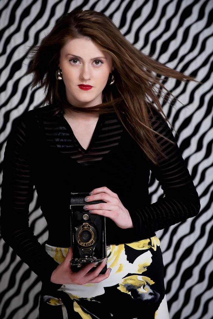 senior model posing with vintage camera during black and white studio model shoot