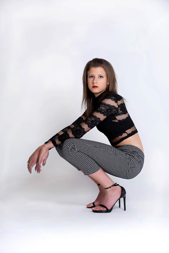 senior girl posing during studio model shoot wearing black and white