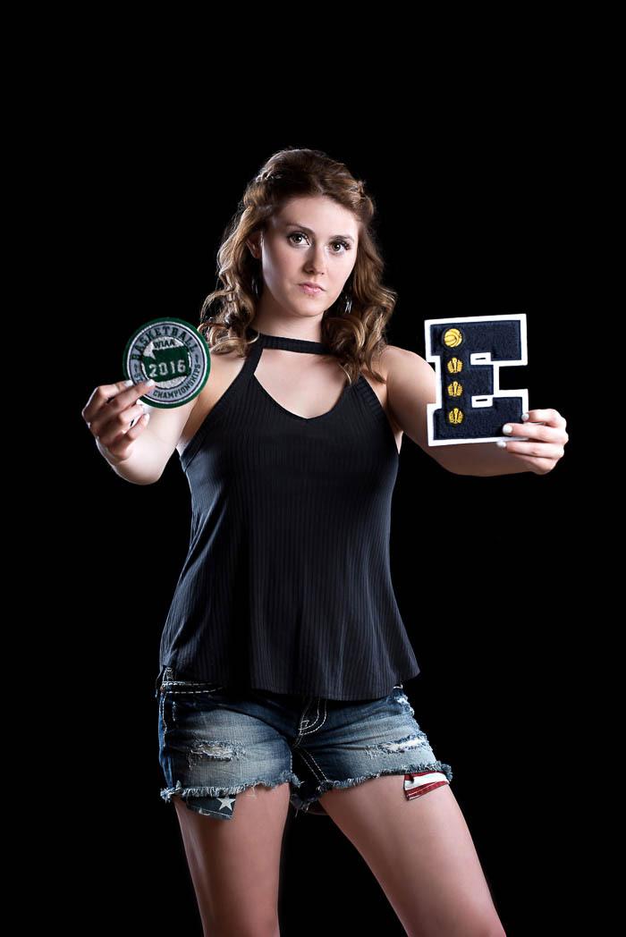 senior girl holding sports letter awards toward camera