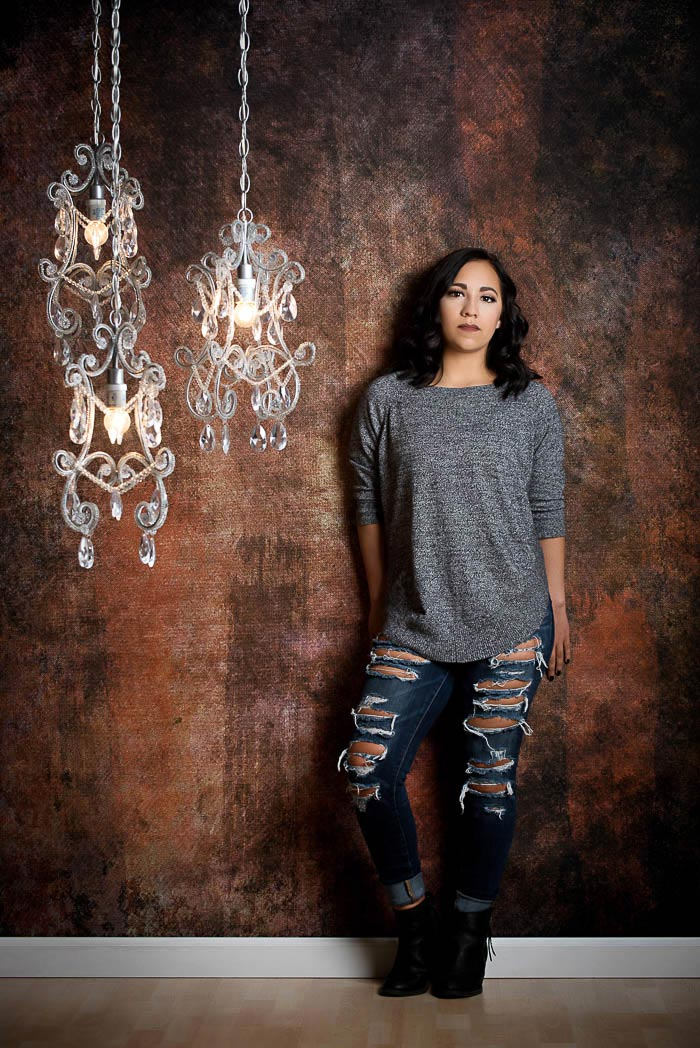 studio senior portrait of girl in torn jeans standing by chandeliers