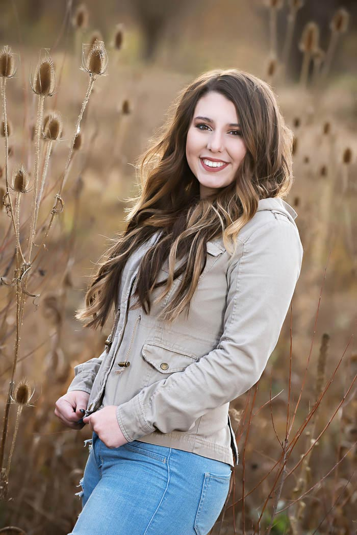 girl standing in wild field during senior picture adventure