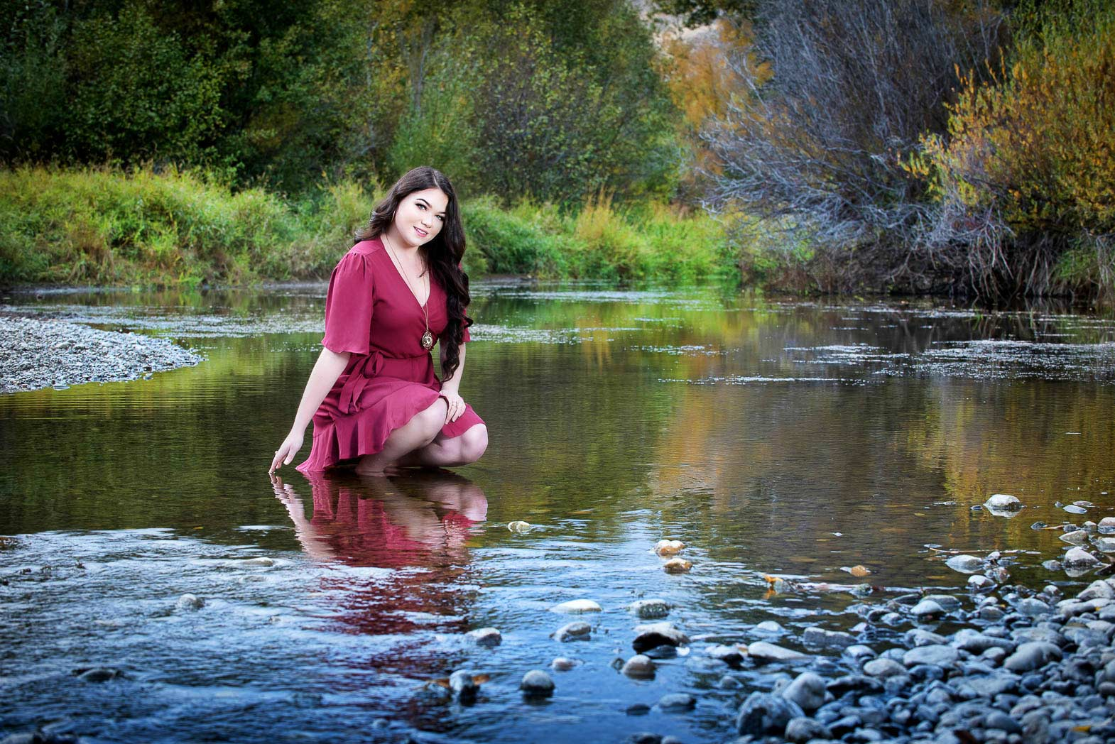 scenic senior picture of girl in red dress kneeling in shallow river with trees reflected in water